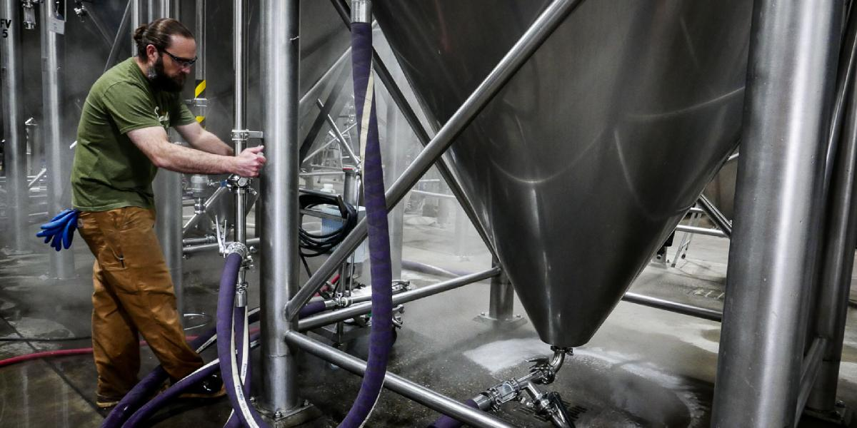Brewer Lynden attaches a hose to a fermenting tank