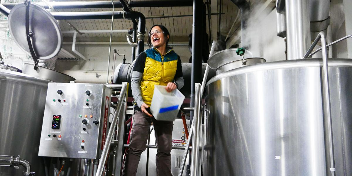 Brewer Tina laughs while adding hops to the boil kettle