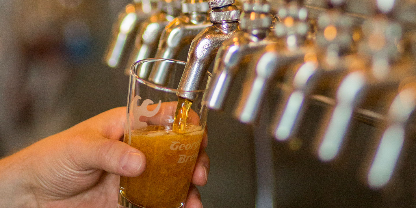 a hand holding a tasting glass being filled with beer from the tap