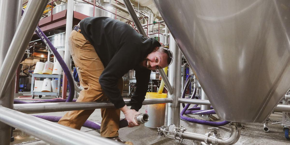 Brewer Thomas attaches a hose to the bottom of a fermenting tank