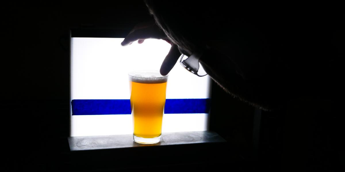 A glass of beer is put in front of a light box to test for clarity