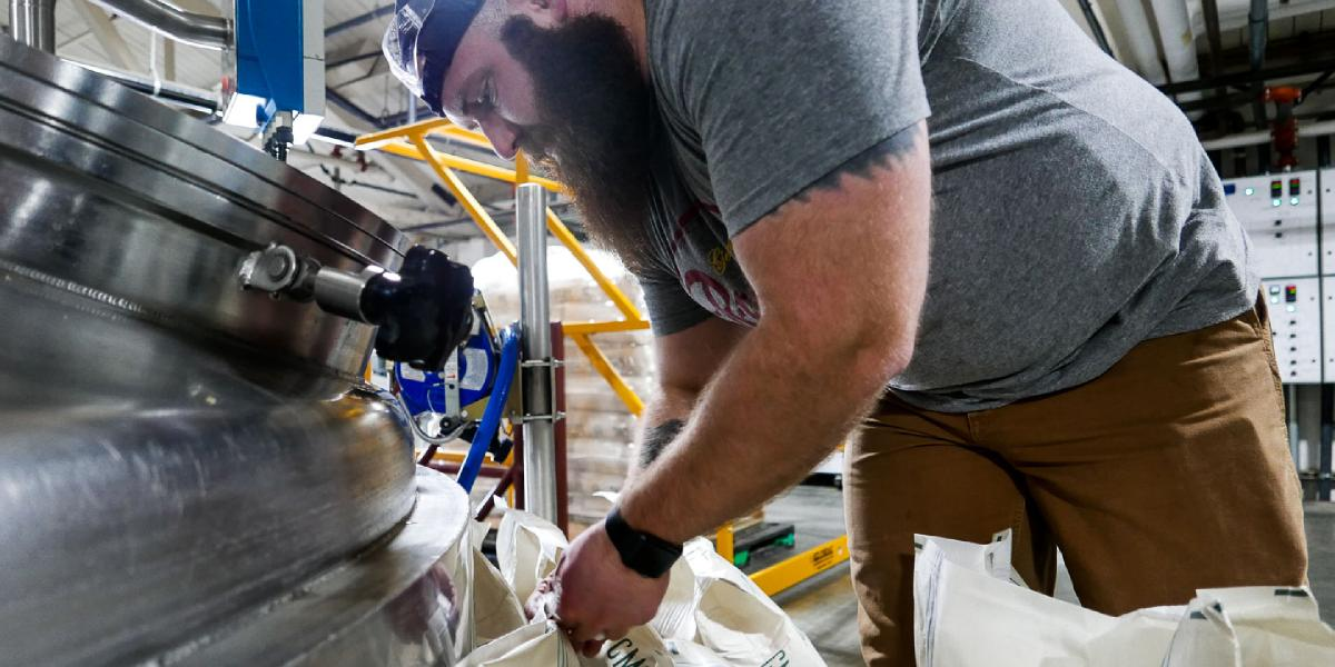 Brewer Rick unties bags of malt in preparation for emptying them into the mash tun